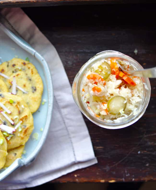 A jar of curtido sitting on a wooden table next to a plate of pupusas with a tan cloth napkin underneath.