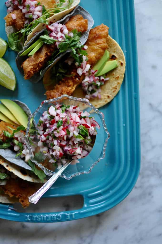 Close up of radish pico de Gallo next to tacos on a blue platter.