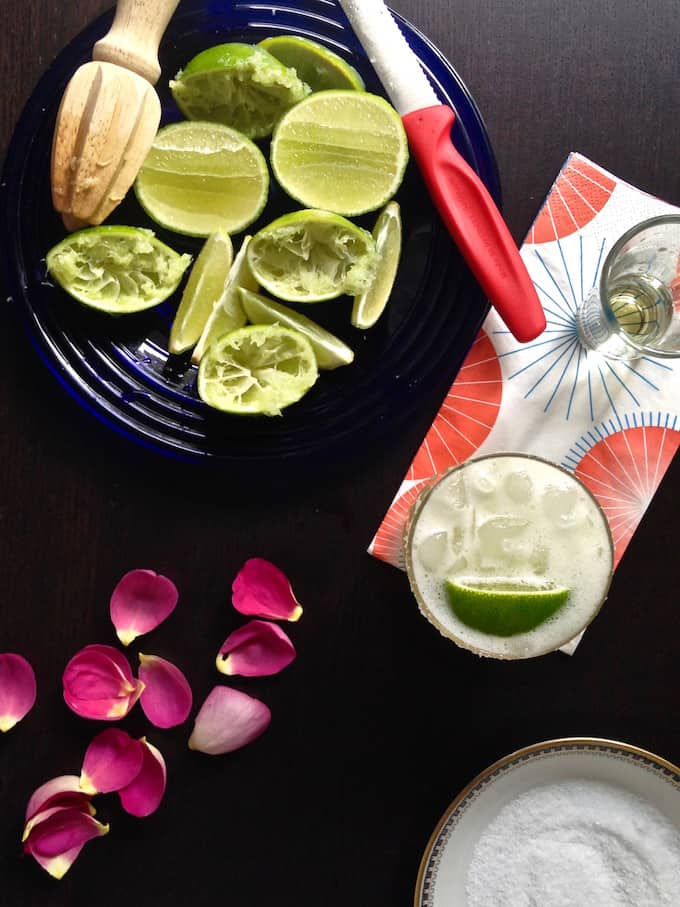 A black table with limes, rose petals, a margarita, and a dish of salt on it.