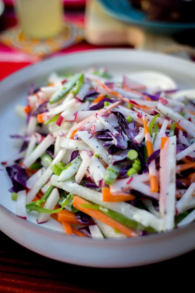 Rainbow Jicama Salad with Poppy Seed Dressing in a white serving dish.