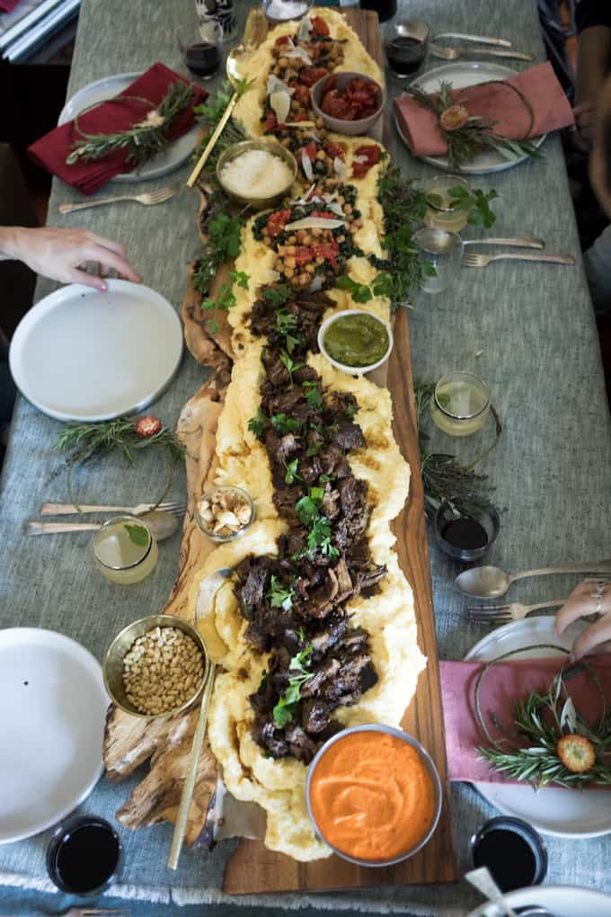 A long wooden tray with polenta on it and different toppings on the polenta sitting on a table.