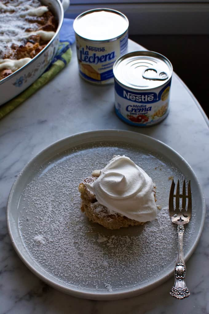 A white plate sitting on a marble table with a piece of Cinnamon Roll Capirotada sitting on it and a fork on the side.
