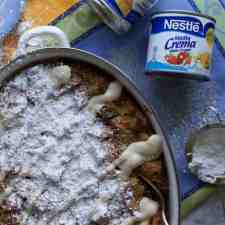Overhead image of Cinnamon Roll Capirotada sprinkled with powdered sugar and a vanilla glaze sitting on a blue and yellow tablecloth.