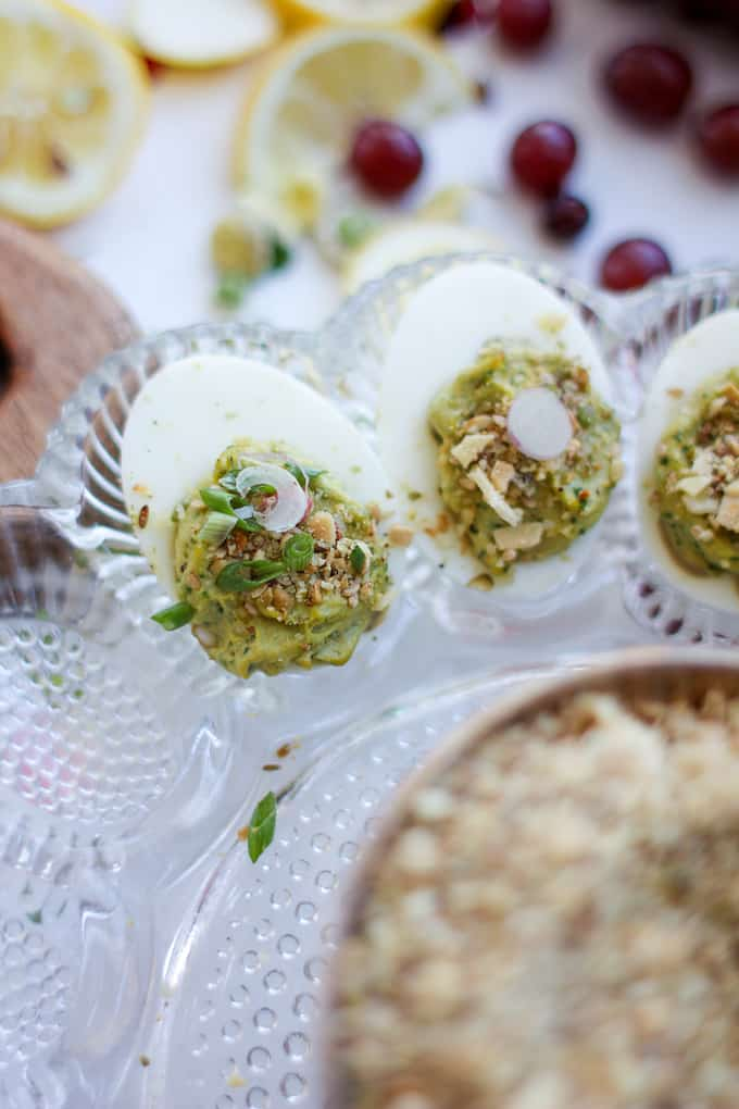 These irresistible avocado deviled eggs are use fresh, ripe avocado instead of mayonnaise. The Egyptian spice blend, dukkah gives them a nutty finish. #avocado #avocadorecipe #deviledeggs #healthymexican