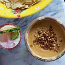 An overhead image of a bowl of salsa de cacahuate or spicy peanut salsa sitting on a marble table with a margarita on the side and some chips.