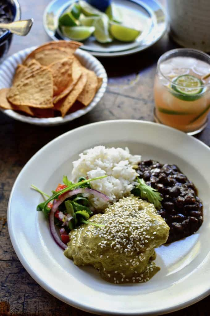 A white plate with chicken mole verde, black beans, white rice, and a salad sitting on a wooden table.