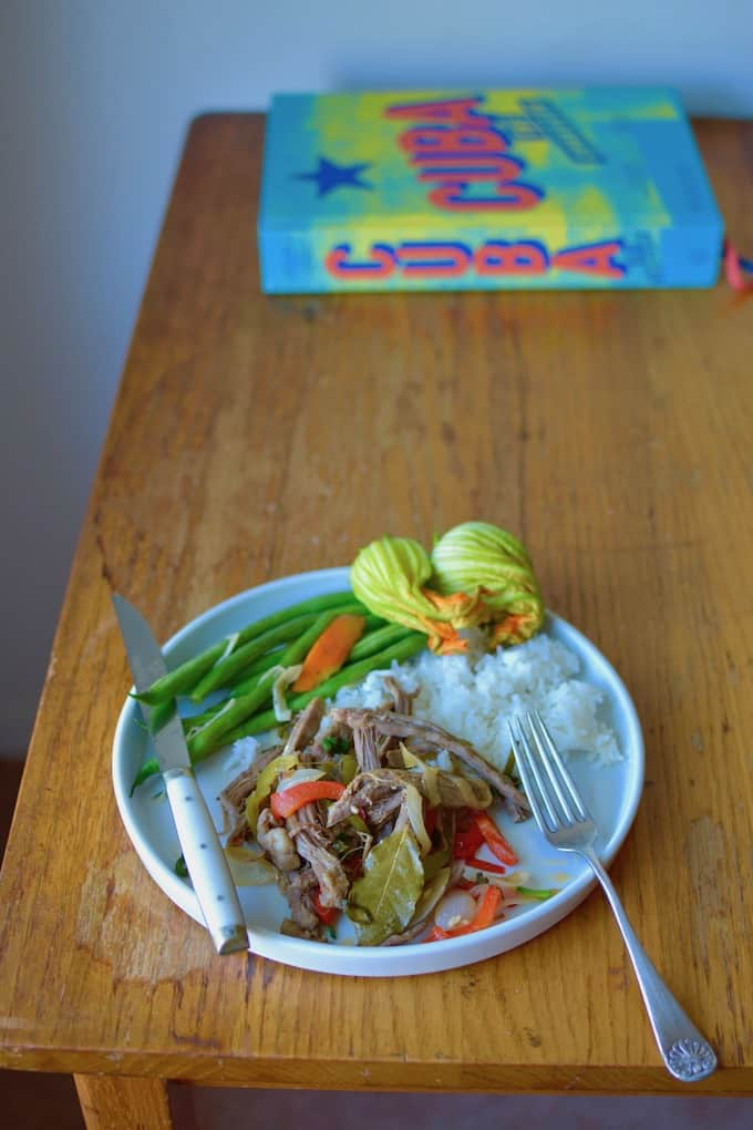 A white plate with Ropa Vieja on it as well as some white rice and green beans sitting on a wooden table.