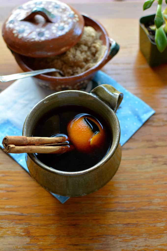 A cup of coffee sitting on a wood table on top of a blue napkin. Inside the coffee is a stick of cinnamon and an orange peel.
