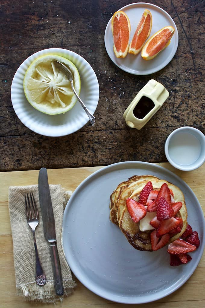 An overhead shot of a plate of pancakes with strawberries on top of them, a half of a grapefruit with a spoon in it and some of the fruit missing.