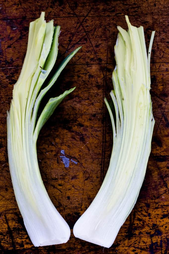 The second step to cleaning leeks is to cut in half vertically and rinse under cold water. #leeks #leekrecipes #howtocleanleeks