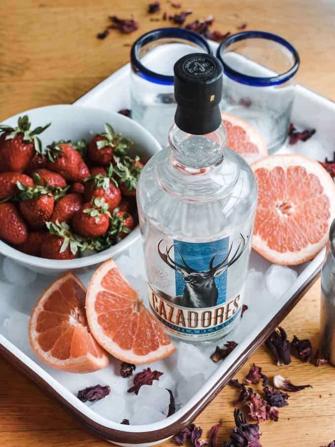 Happy National Tequila Day! This Strawberry Hibiscus Paloma is the essence of summer: Fresh grapefruit juice, floral hibiscus syrup, fragrant strawberries, lime juice, and tequila. #paloma #tequila #ad #tequilacazadores #tequilacocktails #holajalapeno