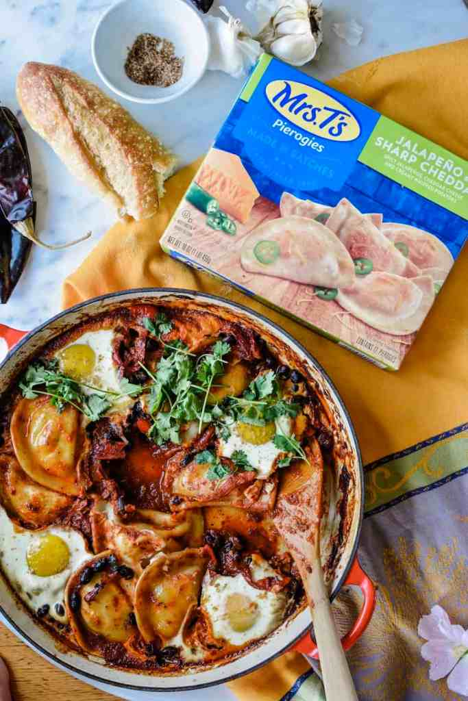 How to make Mexican Baked Eggs with Mrs. T's Pierogies, black beans, roasted red peppers, and silky baked eggs all in a guajillo-charred tomato ranchero sauce. #ad #MrsTPierogies #holajalapeno #bakedeggs #Mexicanbreakfast #pierogies