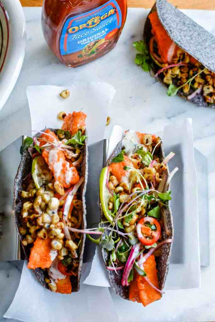 Baked cod fish tacos topped with toasted corn salad and Ortega blue corn taco shells. #ad