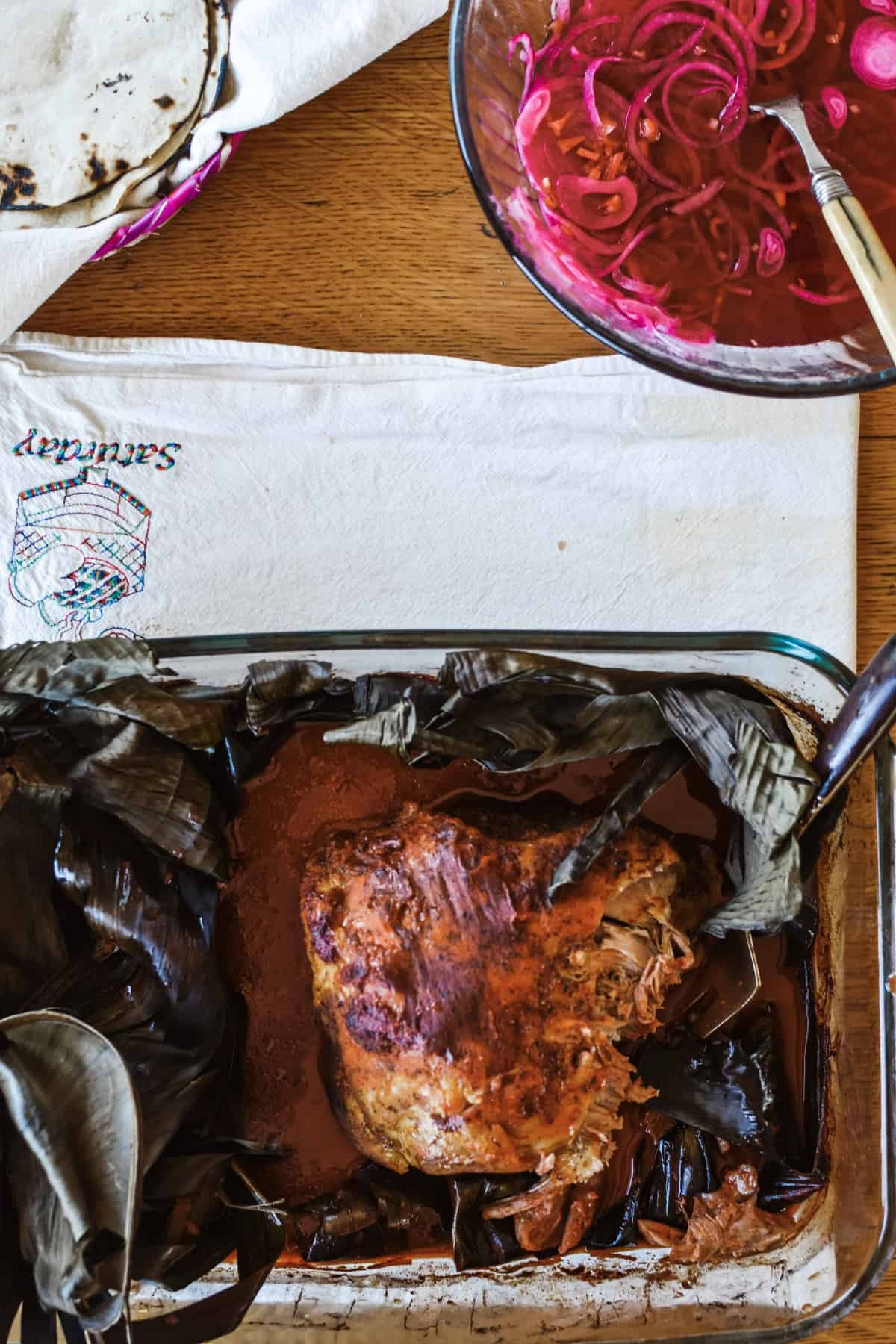 Cochinita Pibil in a baking dish with pickled red onions on a white kitchen towel.