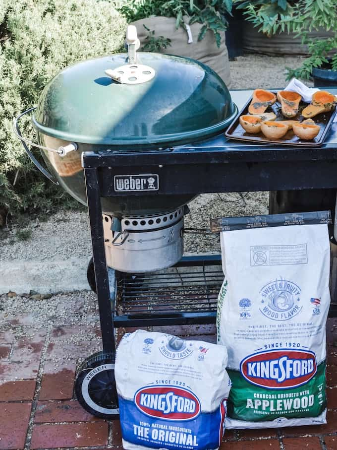 Getting ready to fire up the grill with Kingsford Charcoal. A green grill with two bags of Kingsford Charcoal next to it with a pan of baby squash on top.