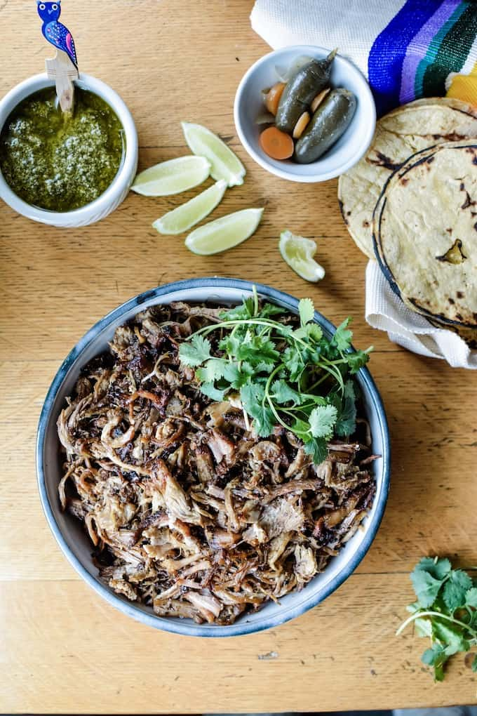 An overhead image of a bowl of pork carnitas garnished with sprigs of cilantro sitting on a wood table with a bowl of salsa next to it.