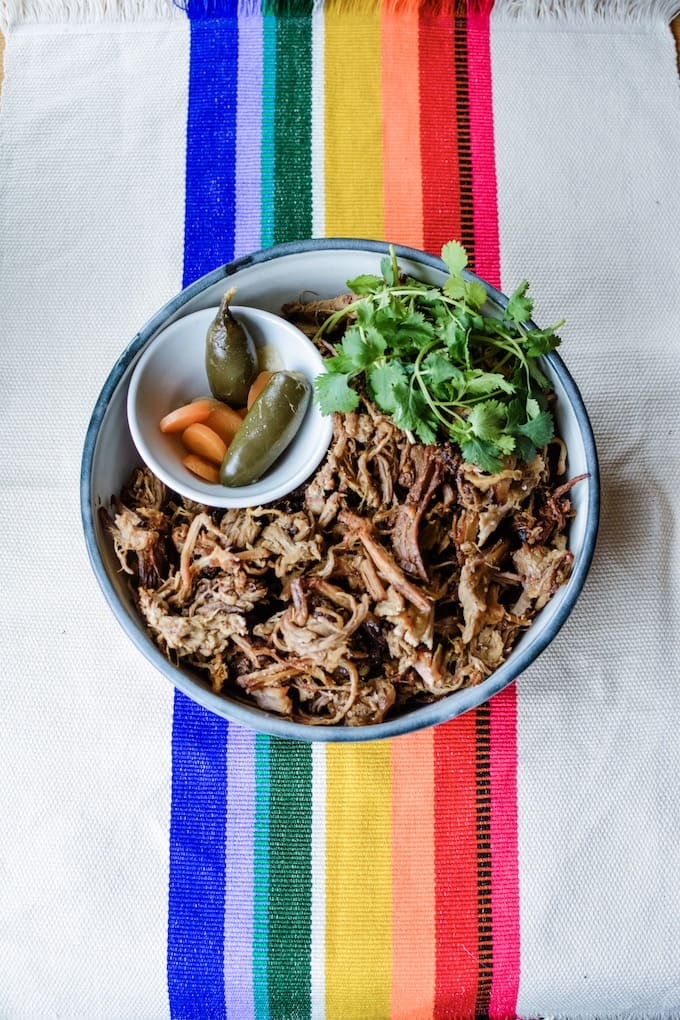 A bowl of pork carnitas garnished with cilantro sprigs and a bowl of pickled jalapeños and carrots sitting inside the bigger bowl.