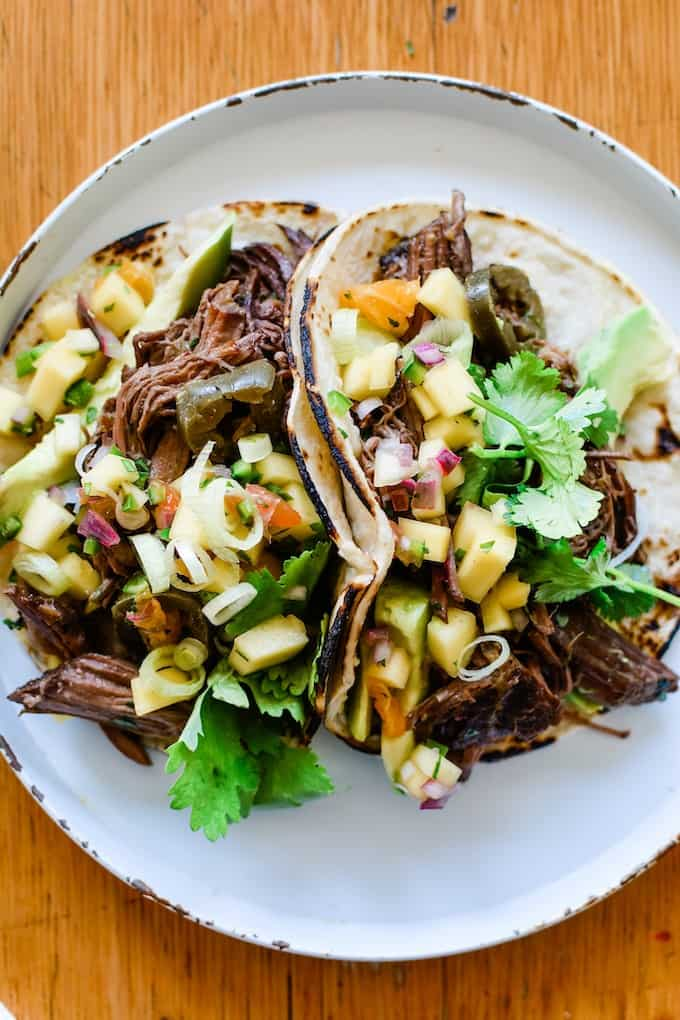 Two beef tacos topped with mango salsa sitting on a white plate on a wooden table.