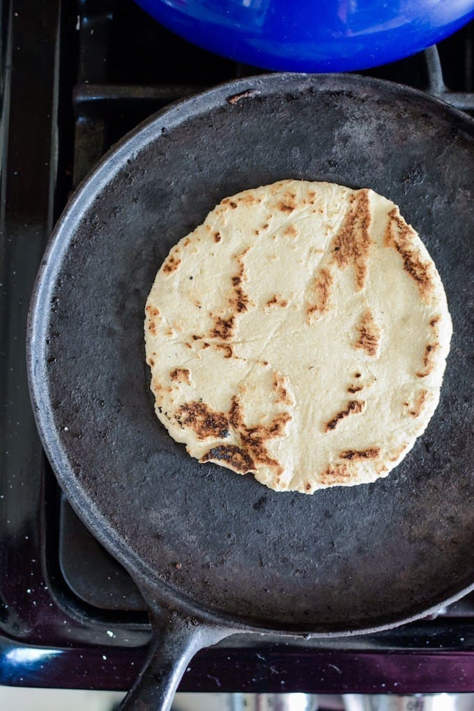 Overhead shot of a corn tortilla cooking in a black pan on the stove top.