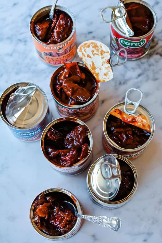 8 opened cans of chipotle peppers in adobo sauce sitting on a marble table some have the lids peeled back and some have the lids completely gone.