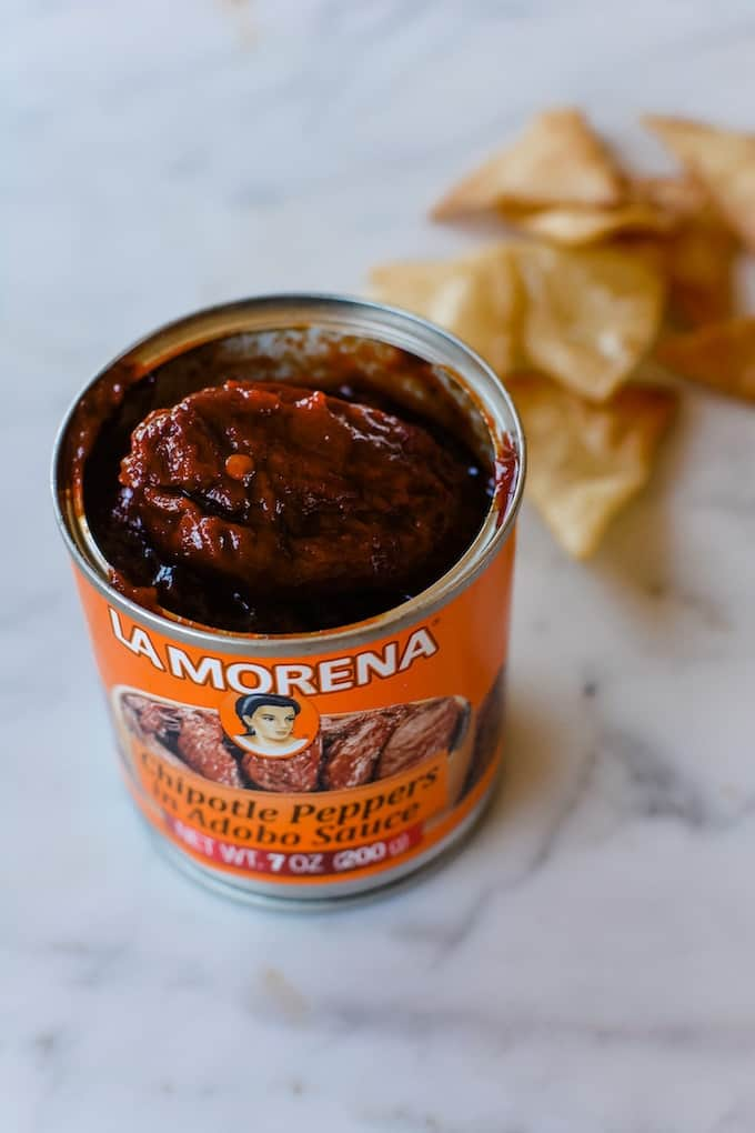 A can of La Morena chipotle peppers in Adobo Sauce that is opened and has a chipotle pepper sticking out of the can.
