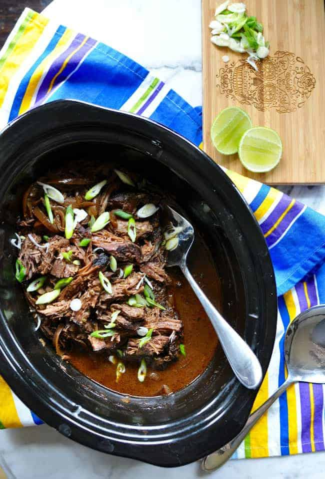 Slow cooker carne adobada just might be your new favorite way to cook a roast. Covered in adobo sauce and slowly simmered until tender, its just delicious! #cincodemayo #adobada #slowcooker #mexicanfood
