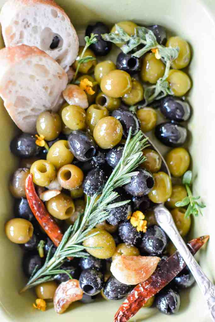 A close-up of a dish of green and black olives with a sprig of rosemary on top and roasted garlic.