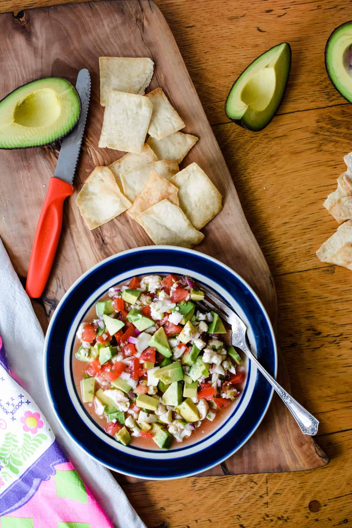 A plate of vegan ceviche with a fork in it sitting on a wooden cutting board next to pita chips.