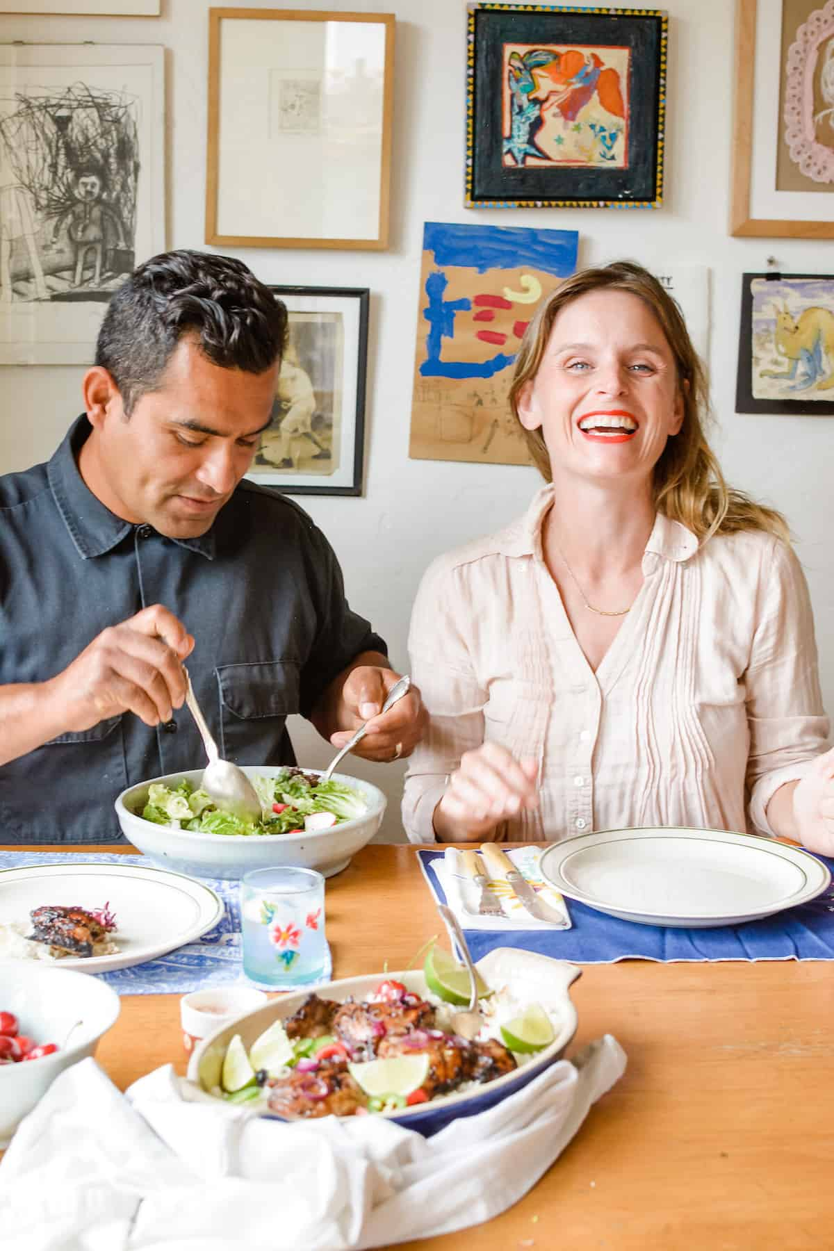 A man and woman sitting at a dinner table laughing and the man is serving salad.