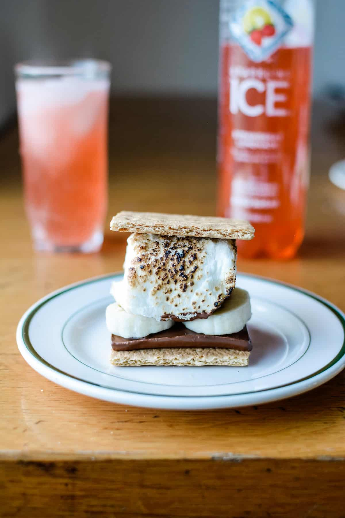 A s'mores dessert made with graham cracker, chocolate, frozen banana slices, and toasted marshmallow on a white plate sitting on a wood table.