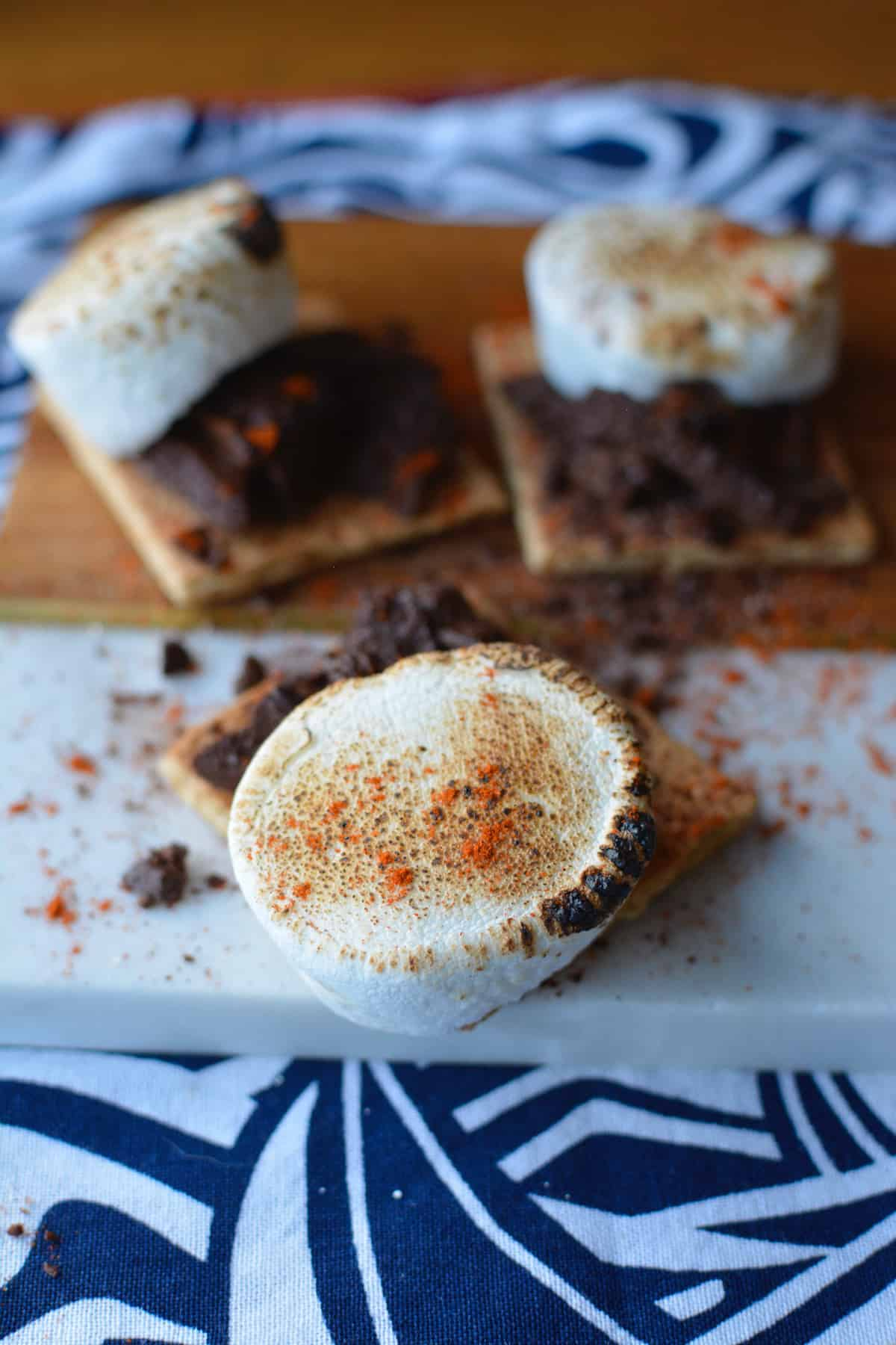 A toasted marshmallow with chili powder on top sitting on a graham cracker with chocolate.