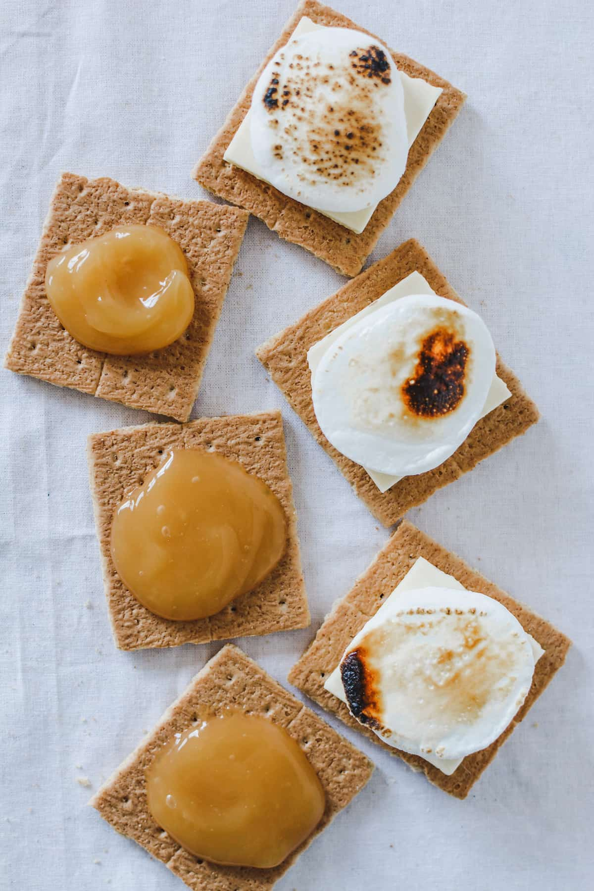 6 half graham crackers on a white tablecloth. 3 have lemon curd on them and three have white chocolate and toasted marshmallow.