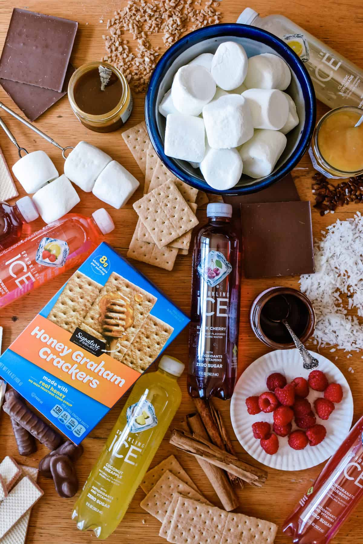 Ingredients for making s'mores on a wooden table, plus bottles of Sparkling Ice.