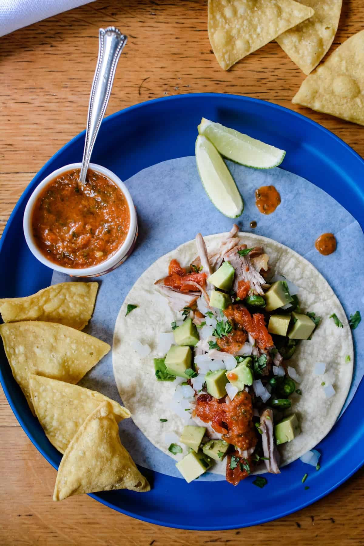 A blue plate with a small dish of salsa, tortilla chips, lime wedges, and a taco on it. The taco is topped with avocado, onions, and cilantro.