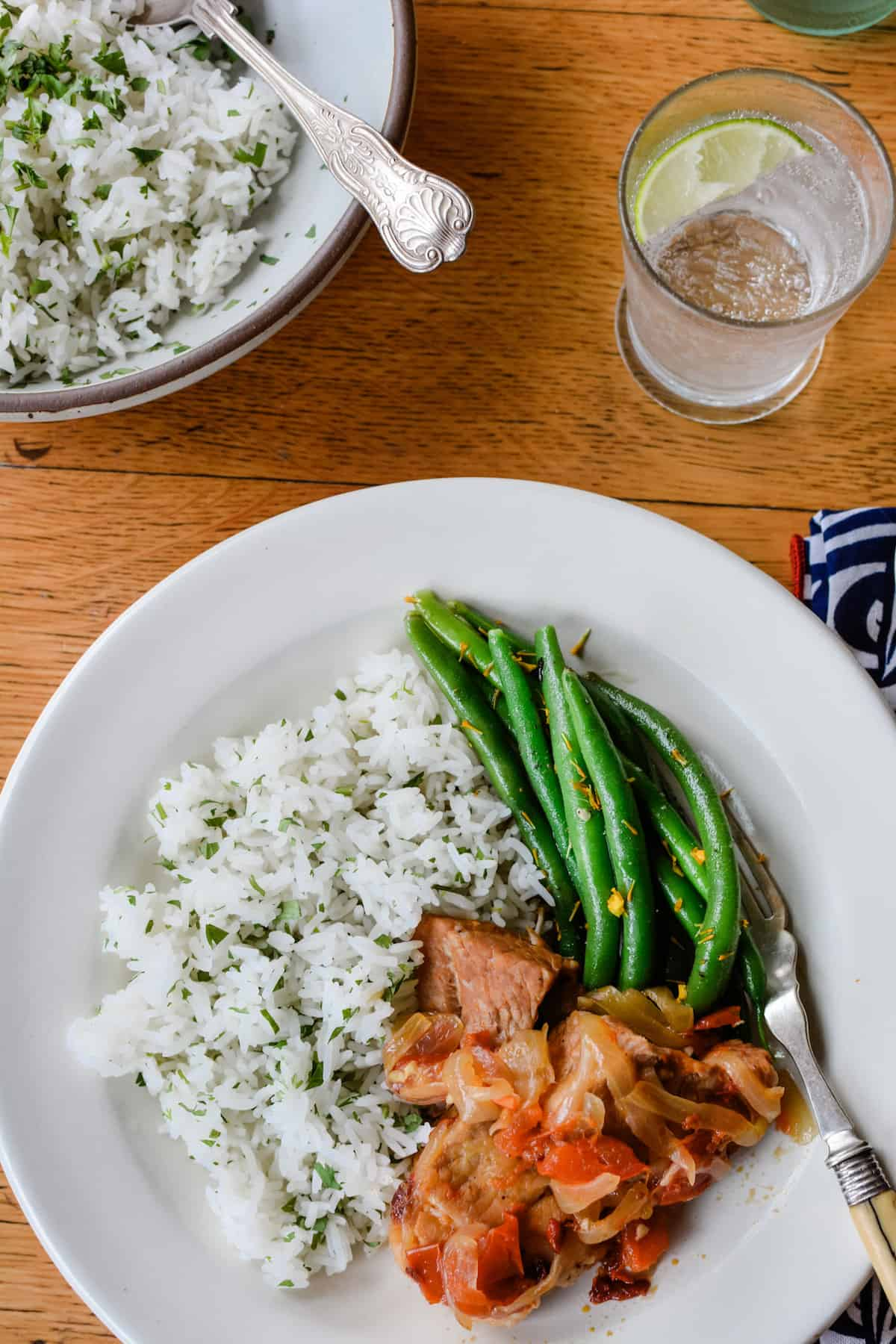 A white plate on a wood table with stewed pork, green beans, and white rice on the plate. A fork is next to the green beans.