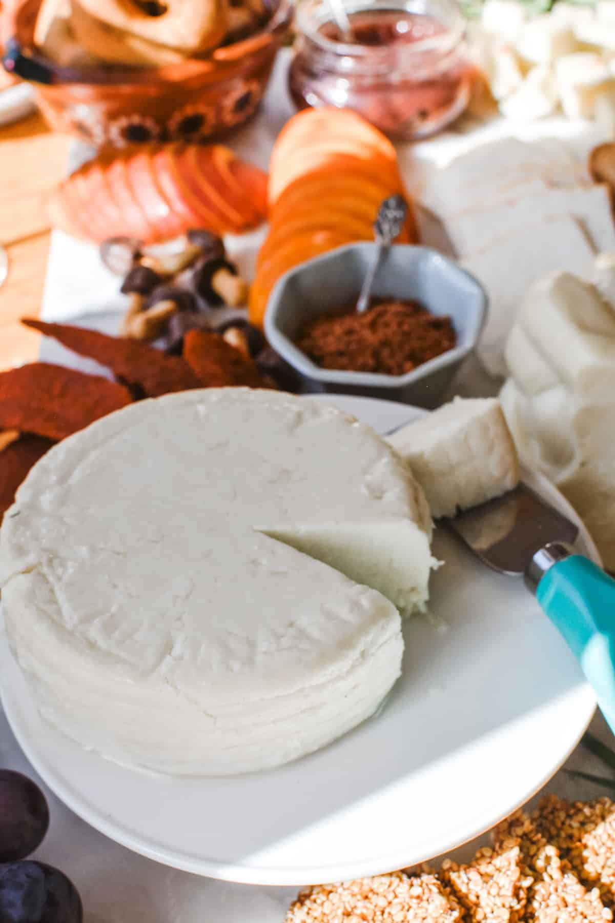A wheel of white cheese with a piece cut out and sitting on a cheese knife with a light blue handle sitting on a marble slab with snacks on it.