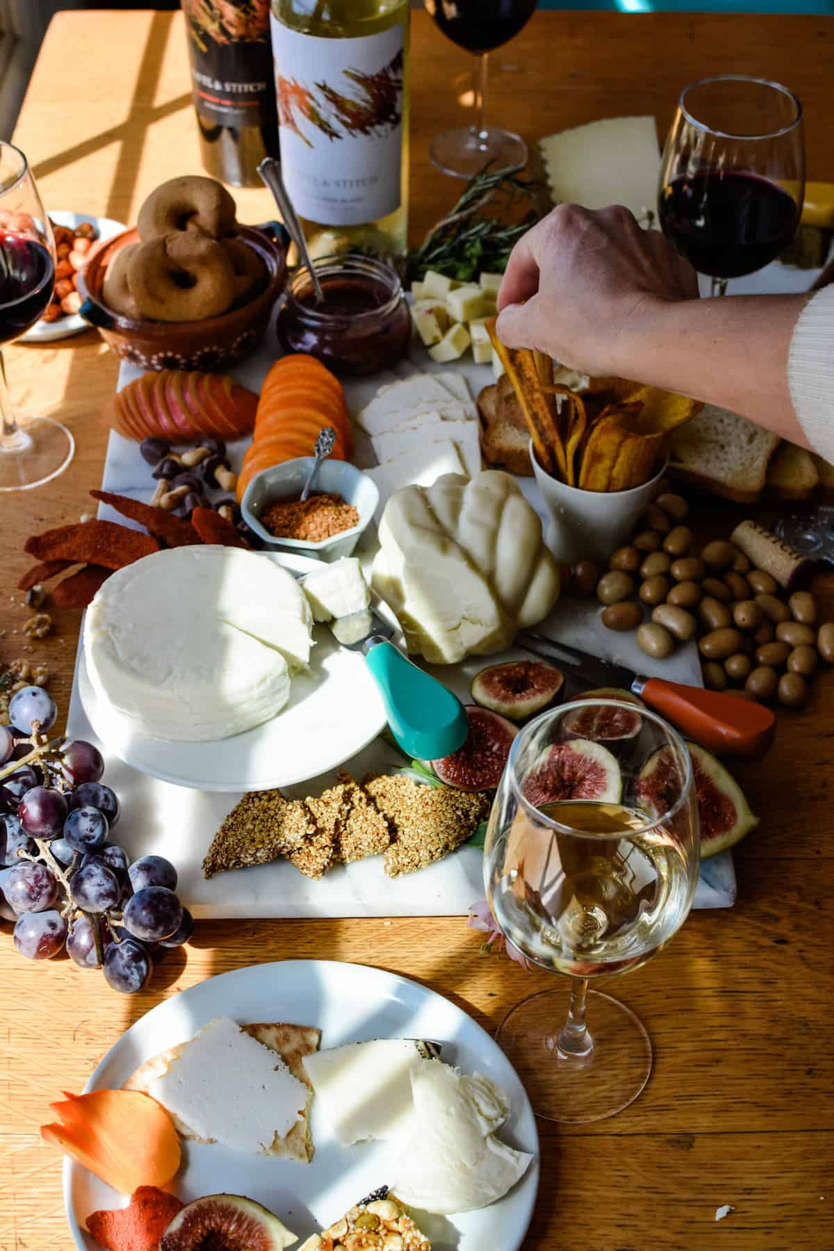 A white plate filled with cheese and snacks and a glass of white wine sitting on a wooden table next to a cheese board filled with cheese.