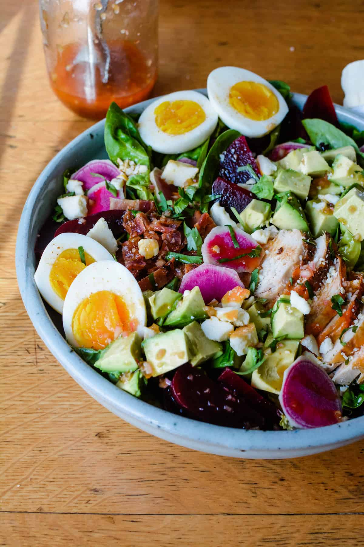 A large Cobb Salad recipe with hard boiled eggs, beets, chicken, and bright pink radishes.