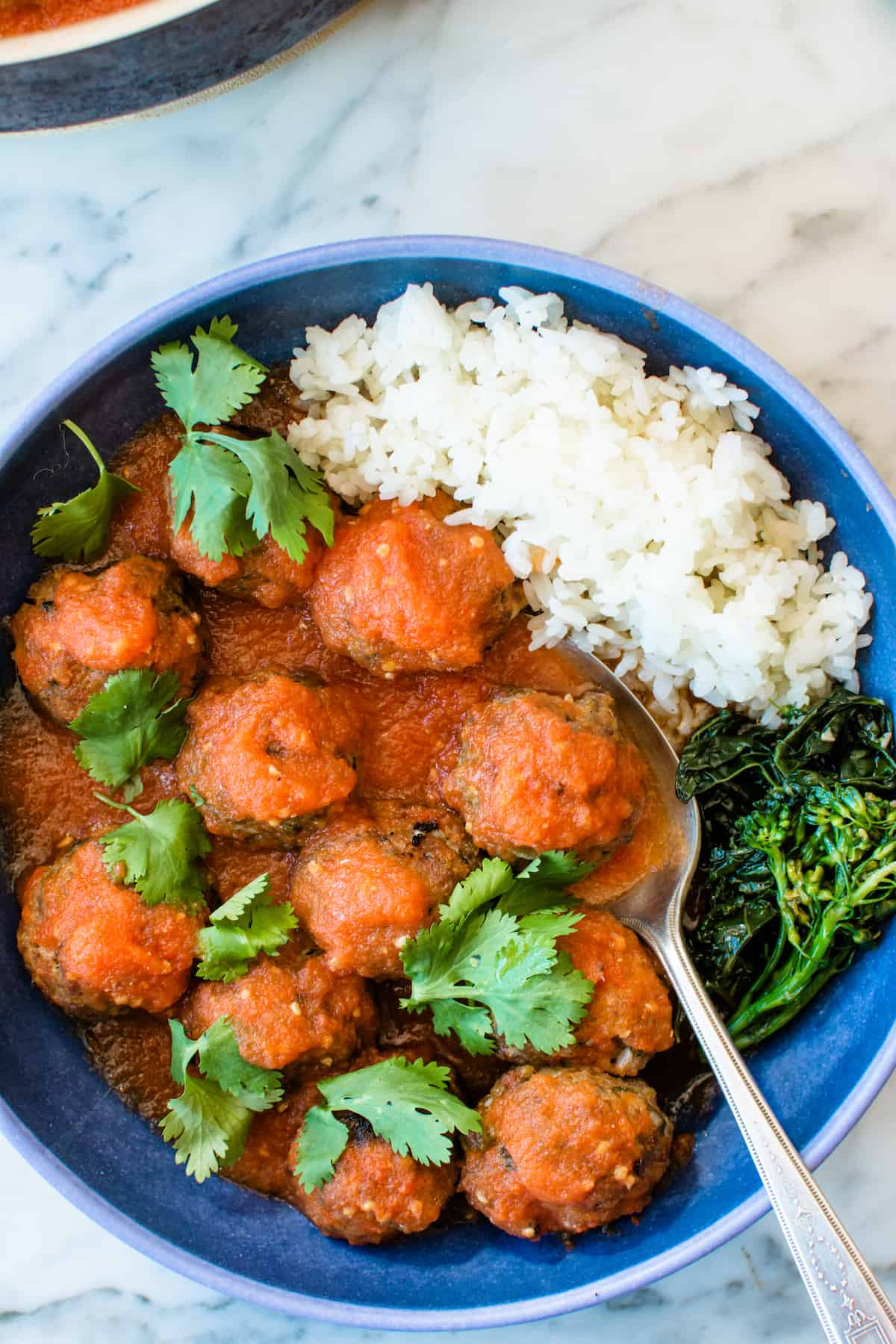 Overhead image of a blue bowl with meatballs in tomato sauce in it along with some white rice and green vegetables sitting on a marble table.