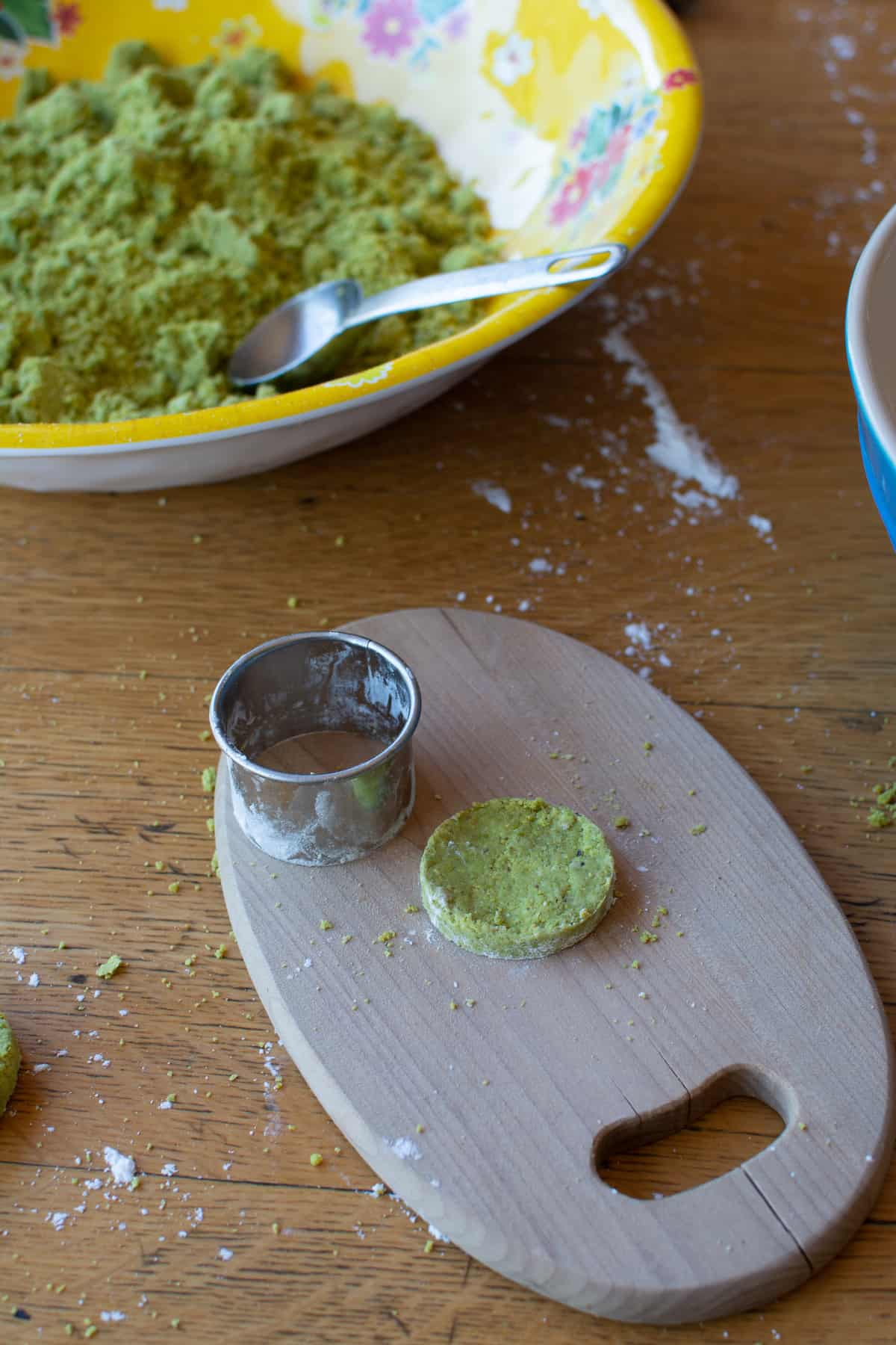 Pistachio mazapan after being formed into a round shape with a biscuit cutter sitting to one side on a small wood cutting board.