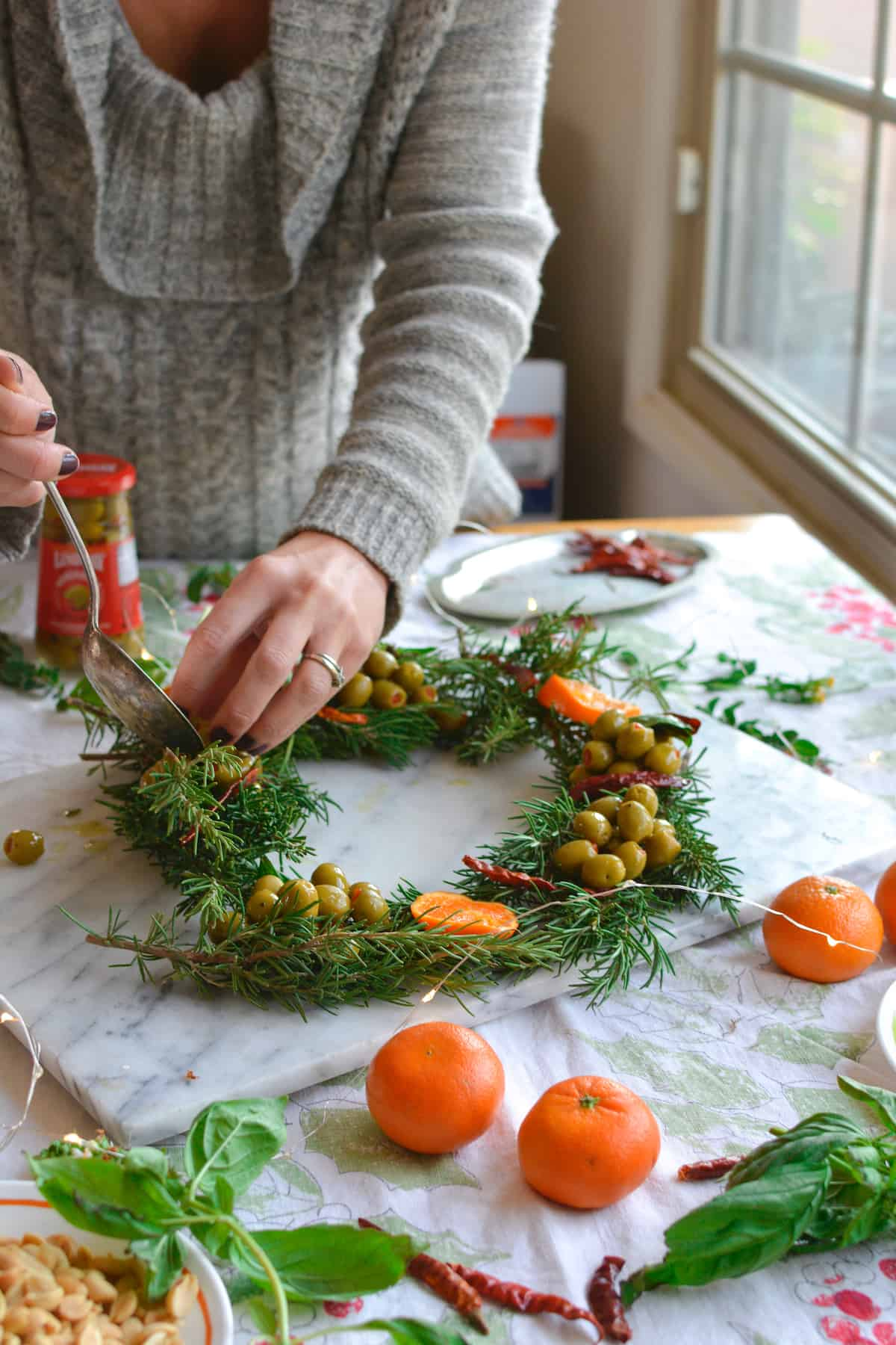 Woman arranging rosemary sprigs and olives on a marble platter to create a wreath shaped appetizer.