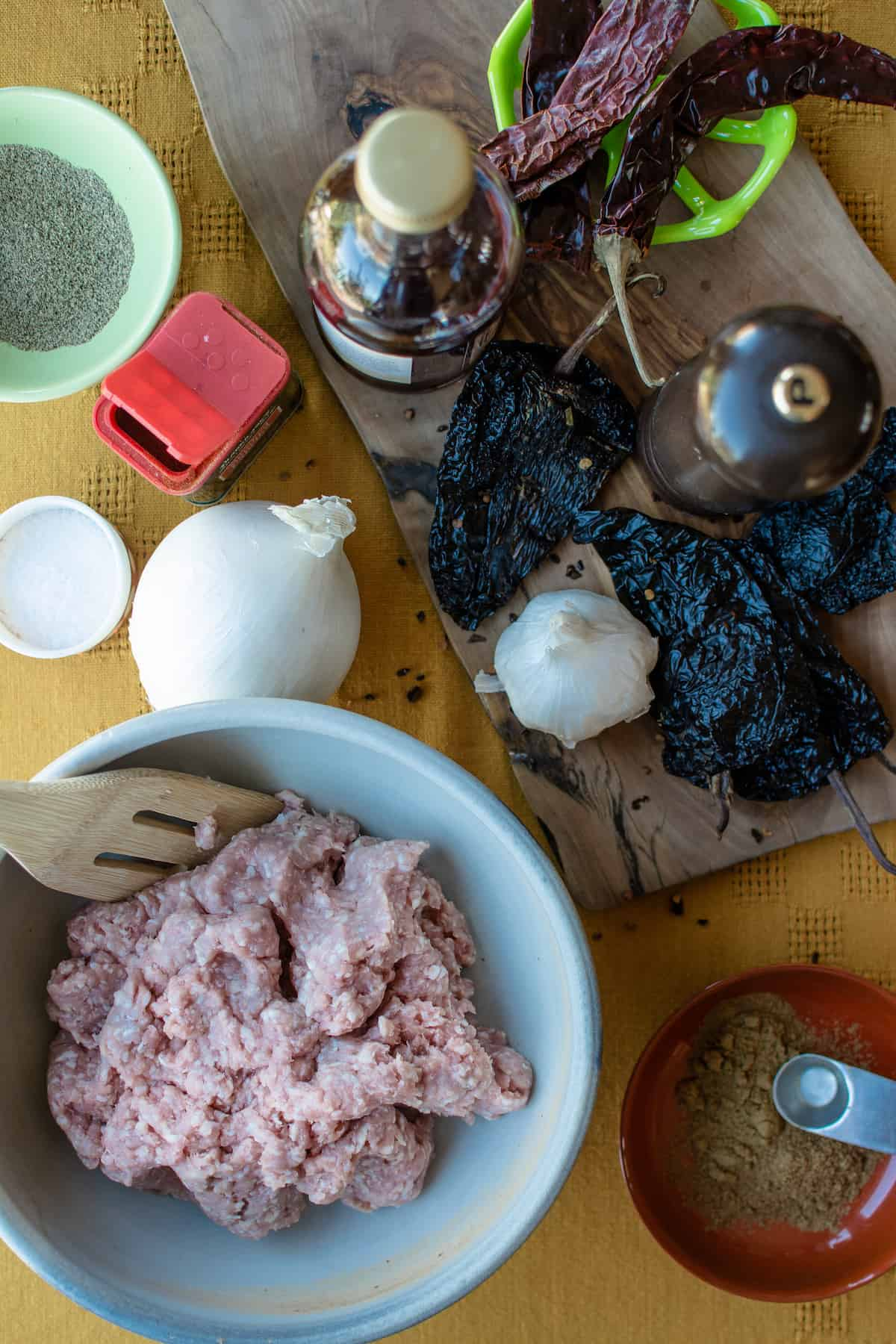 Ingredients to make chorizo on a table with a yellow tablecloth. Ground pork in a bowl alongside an onion, dried chiles, and spices.