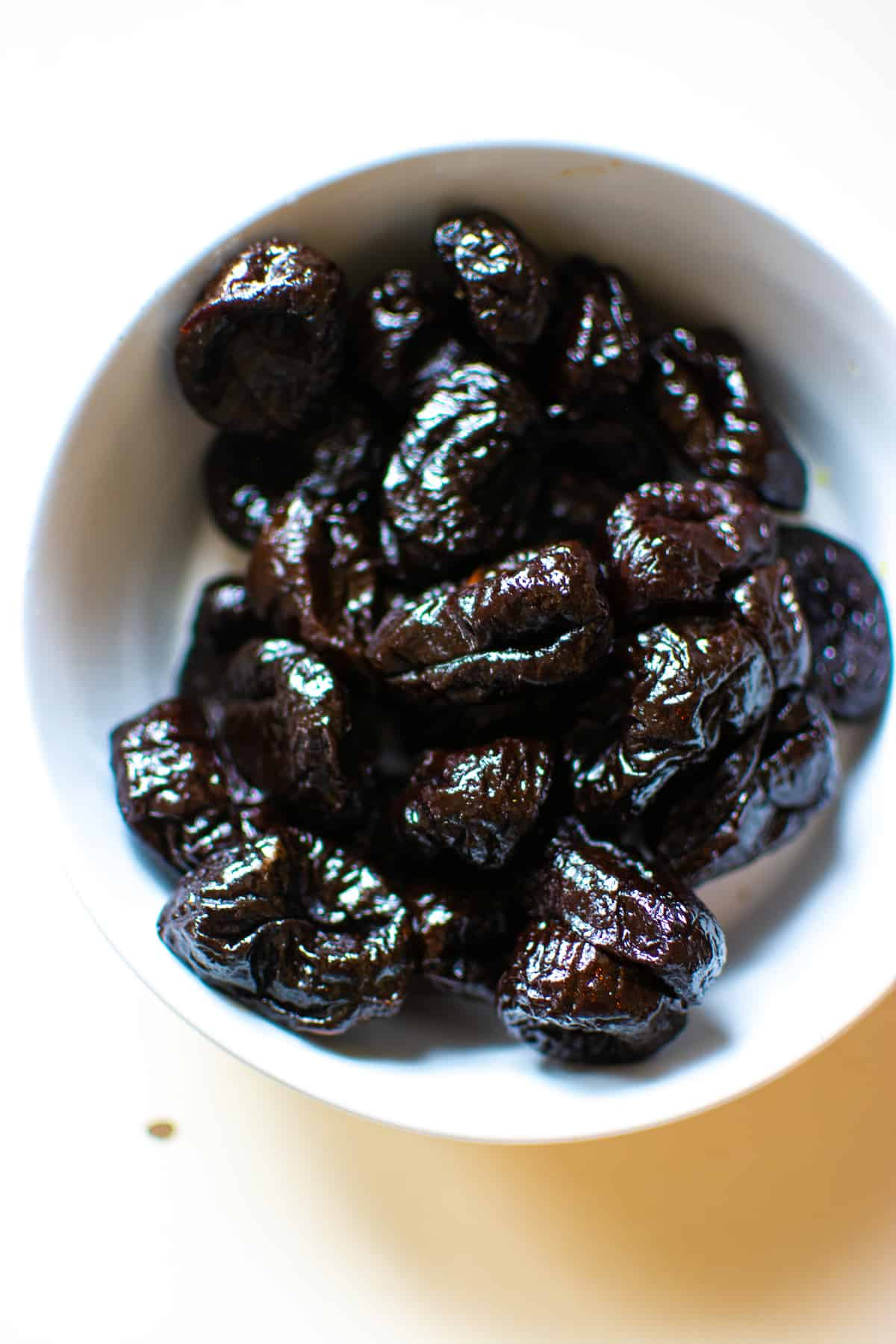 A bowl of prunes sitting on a white counter.