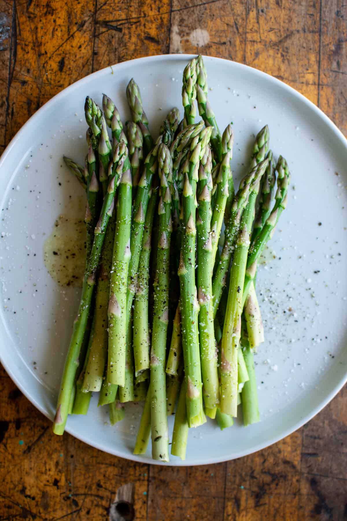 A white plate with raw asparagus on it that has been tossed in olive oil, salt, and pepper.