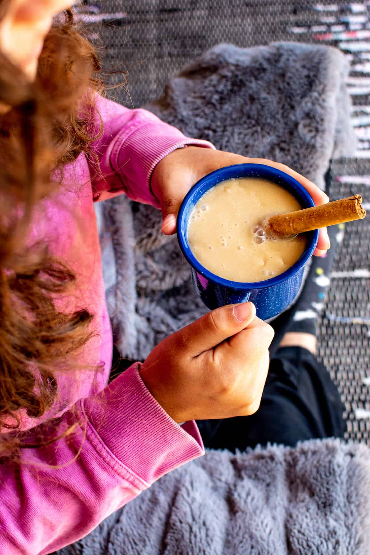 A girl in a pink sweater with a blanket wrapped around her holding a blue mug filled with atole and a cinnamon stick sitting in the mug.