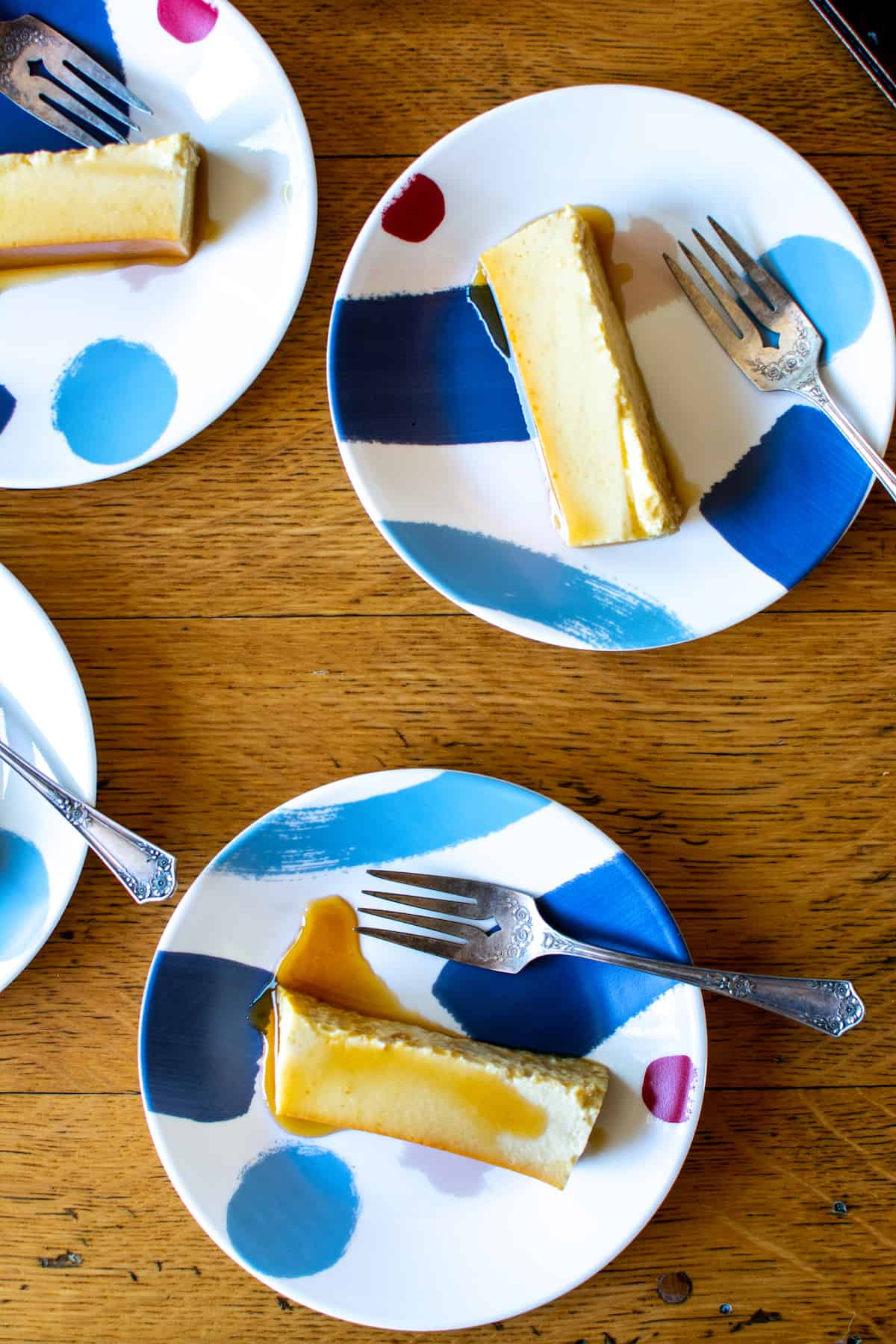 Blue and white dessert plates with pieces of flan on them and forks on the plates.