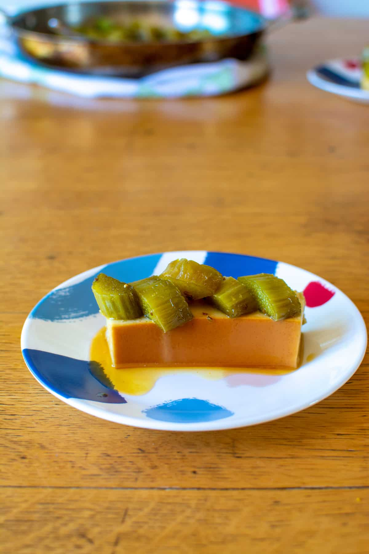 A piece of flan sitting on a blue and white dessert plate with pieces of green rhubarb sitting on top on a wood table.