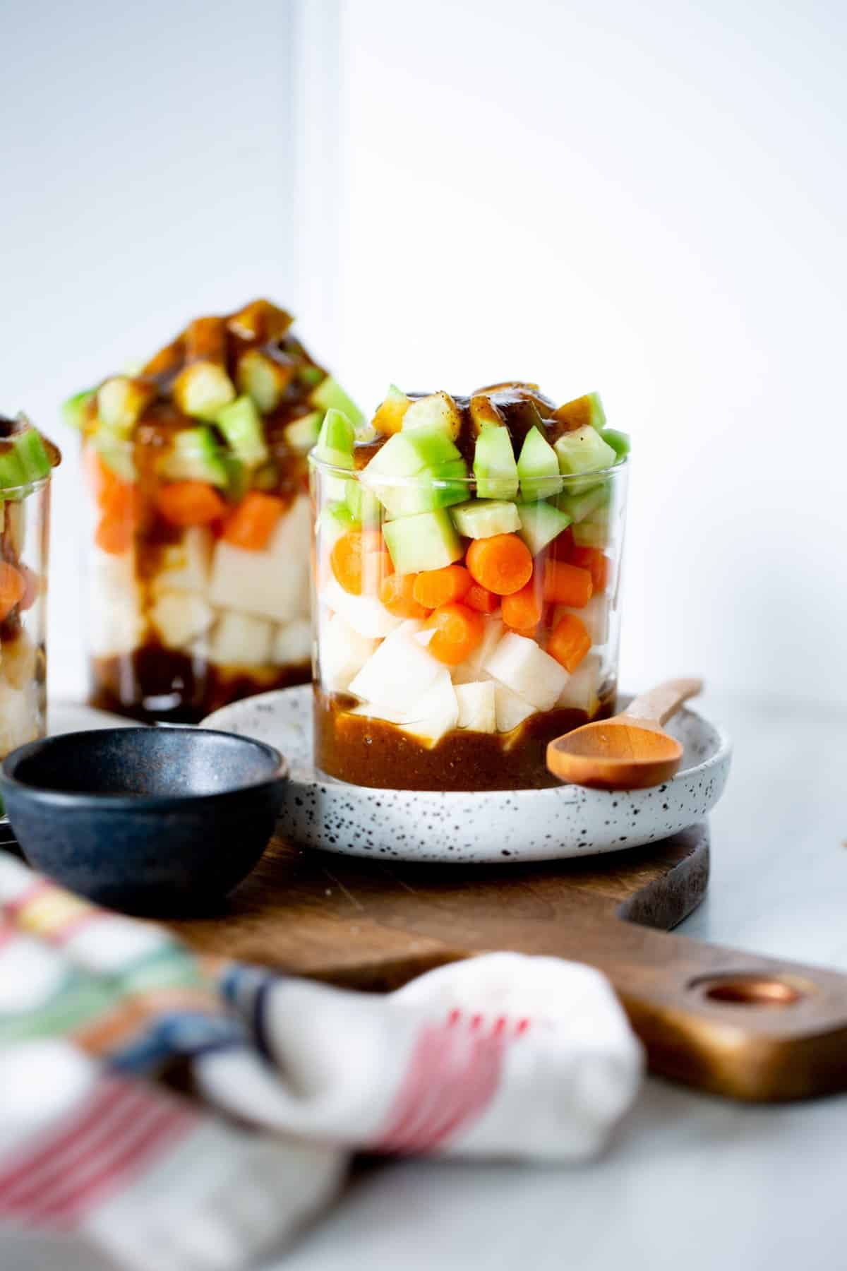 Glasses filled with chopped vegetables including jicama, carrots, and cucumbers on a wood board, with a wood spoon.