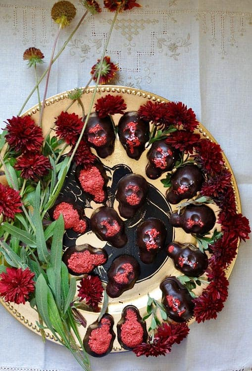 A gold platter with chocolate calavera or skulls for day of the dead. Flowers surround the skulls and the platter is sitting on a white tablecloth.