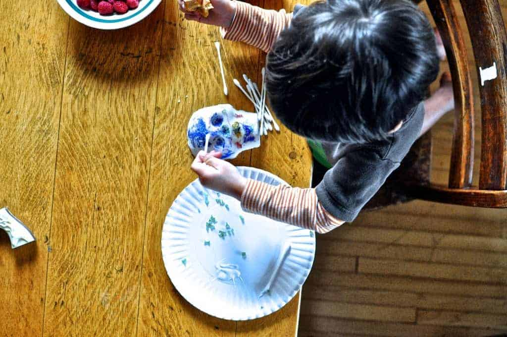 A small child sitting at a wood table decorating a sugar skull with paint on a Q-tip with a bowl of raspberries next to him.